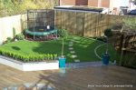 Garden was very unusable with Multiple steps from back doors new deck with inset sandstone sunflower feature was installed with new block rendered planter wall planted with topiary and linking circle lawns edged with granite setts and separate children's