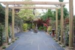 Small town house garden with a Japanese feel black limestone random paving installed with a centre slate water feature, Timber arbour constructed and garden planted with feature plants