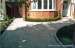 AFTER: Driveway constructed using Tegula paving with sweeping curved path to front door and feature band across drive mouth, new wall, lawn and planting installed.