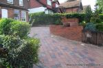 AFTER: Driveway installed with Tegula paving laid at 45 degree to property with in set lighting and feature wall merging into timber wall along front garden and road boundary