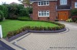 Driveway constructed using pewter grey paving with contrasting colour band and feature curved double row of kerbs with Topiary hedge to retain level change & inset LED lights