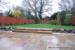 Tired garden received a complete new design Patio installed with 4 size sawn sandstone paving edged with firestone rocks and alpine planting, steps built with sawn sandstone uprights and sawn sandstone bullnose treads, New lawn installed in 3 rings all ed