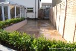 patio was constructed useing fossil sandstone in 4 sizes laid to a random pattern with a curved block planter wall painted in gun ship grey and planted with a topiary hedge.