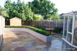 AFTER: New lawn and planting new fence and shed patio was constructed useing fossil sandstone in 4 sizes laid to a random pattern with a curved block planter wall painted in gun ship grey and planted with a topiary hedge.