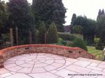AFTER: Feature tumbled sandstone circle in cased with old stock brickwork with double bullnose on top