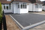 New driveway installed using granite paving with contrasting colour band and inset lights
