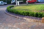 Driveway constructed using Marshall's Tegula paving with contrasting colour band and feature curved double row of kerbs with Topiary hedge to retain level change.