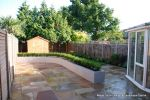 New lawn, planting, shed and fence patio was constructed using fossil sandstone in 4 sizes laid to a random pattern with a curved block planter wall painted in gun ship grey and planted with a topiary hedge.